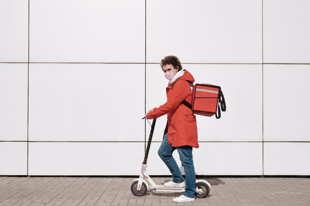 A person wearing a mask and riding an electric scooter