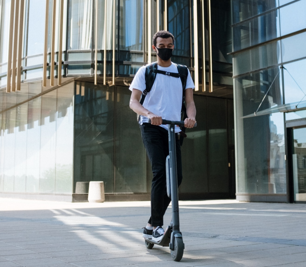 A person wearing a black mask and moving around in an e-scooter