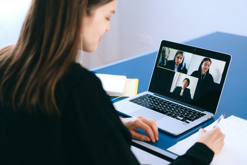 A person communicates with others via video call on a laptop